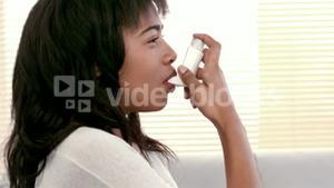 Woman using asthma inhaler at home