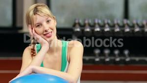 Fit woman smiling at camera in gym