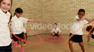 Pupils exercising with hula hoop