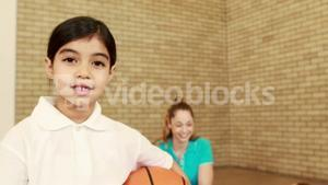 Smiling girl with thumbs up holding basketball