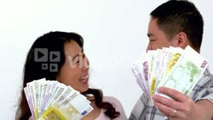 Happy Asian couple showing his money
