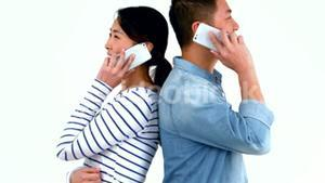 Smiling couple having phone calls back to back