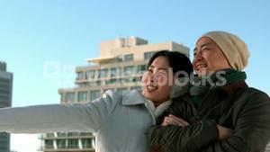 Loving Asian couple in winter clothes pointing at somethings