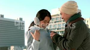 Loving Asian couple in winter clothes engaging