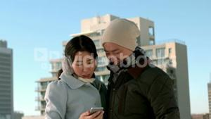 Couple in warm clothes using mobile phone