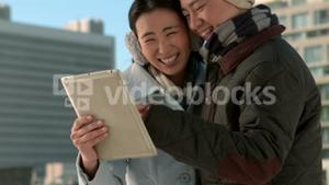 Couple in warm clothes using tablet