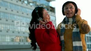 Couple in warm clothes enjoying music together