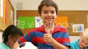 Boy with thumbs up holding a ball