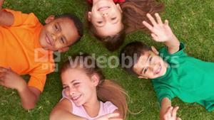 Smiling children lying in circle