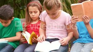 Children reading books at the park