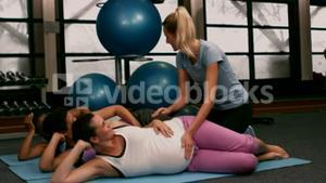Fitness trainer helping pregnant women train