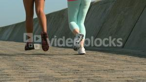 Two fit women running together