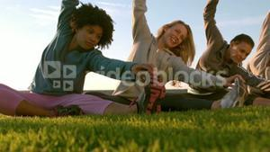 Smiling sporty women stretching during fitness class