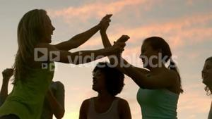 Happy sporty women cheering against sunset