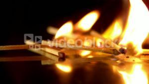 Lit matches falling on black background
