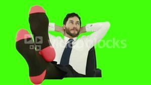 Businessman relaxing in his chair with legs up and with no shoes