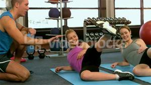 Fit women excercising at the gym with trainer