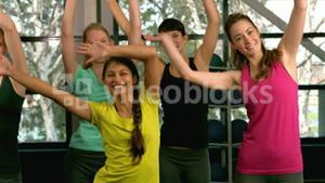 Fit woman group doing aerobic exercises at the gym