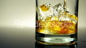 Pouring Whiskey on Ice in glass