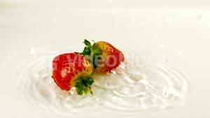 Two strawberries falling into water