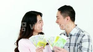 Happy couple showing money