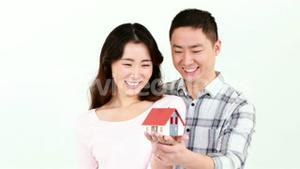 Happy couple holding a little house on their hands