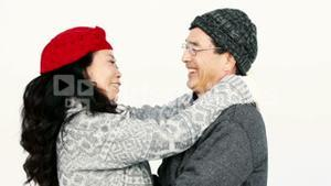 Mature Asian couple hugging and talking