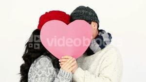 Mature Asian couple covering their face wit a pillow heart