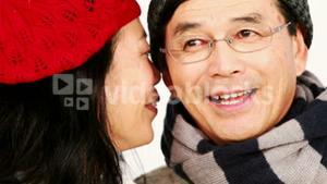 Mature Asian couple holding coffee cups and talking
