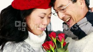 Mature Asian couple holding roses