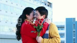 Asian man giving roses to his wife