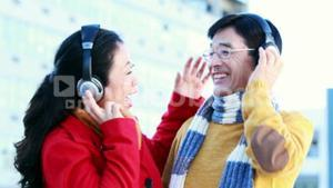 Mature Asian couple listening to music with headphones