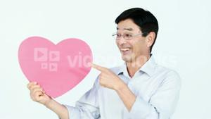 Smiling Asian man holding a pink heart