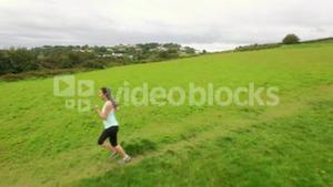 Fit woman running in a green landscape