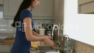 Pretty young woman washing hands in the kitchen