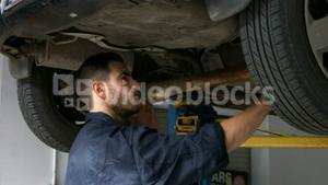 Handsome mechanic overhauling a car while having a phone call