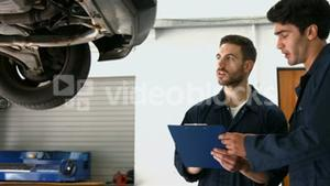 Handsome mechanics overhauling a car