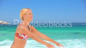 Blonde girl playing with a beach ball