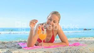 Woman drinking a cocktail on a beach