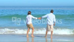 Cute couple playing at the edge of the water
