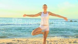 Woman doing yoga on a beach