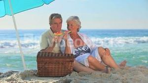 Elderly couple eating watermelon on a beach
