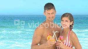 Couple posing with cocktails on a beach