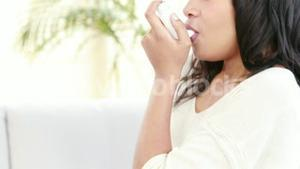 Smiling woman using asthma inhaler at home