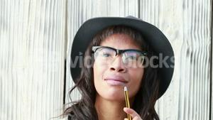 Smiling hipster woman with pencil
