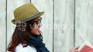 Smiling hipster woman reading a book
