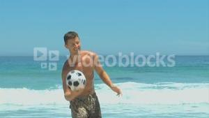 Man coming out of the sea to pick up a soccer ball