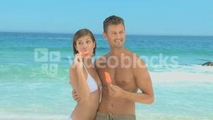 Beautiful couple eating orange water ices
