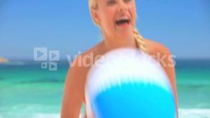 Attractive blonde woman playing with a beach ball