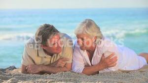 Elderly couple lying on a beach